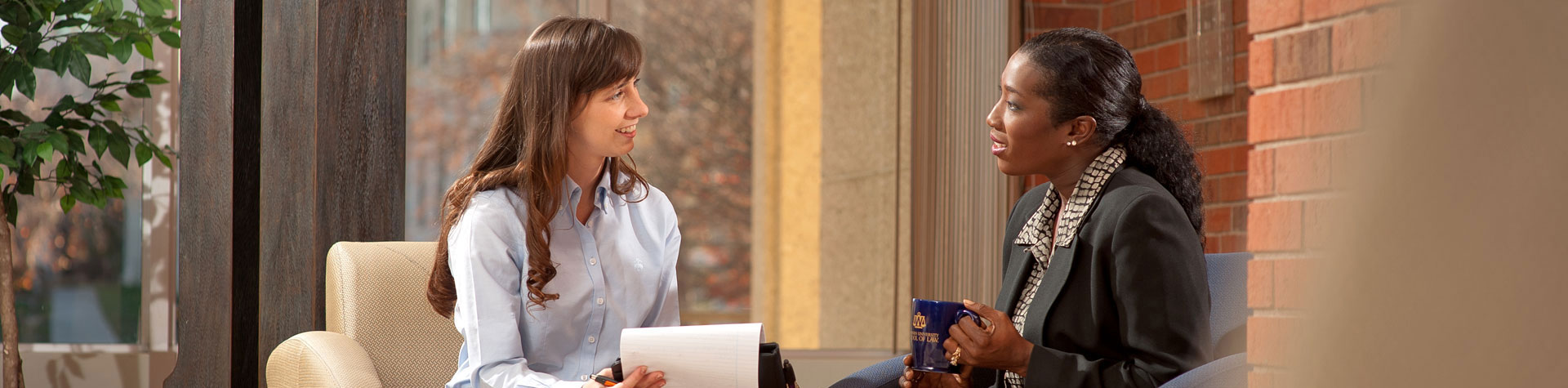 Photograph: Current law student visiting with a Washburn Law graduate.